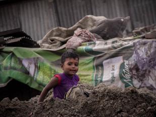 Street Photography little Nepali boy in dirt heap in Kathmandu