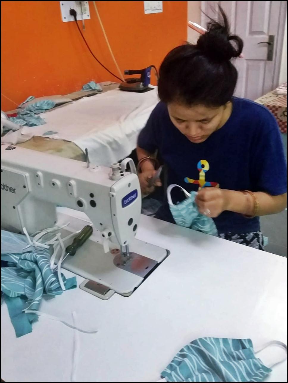Eine junge Mitarbeiterin beim Maskennähen