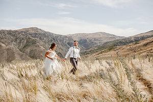 Bride and Groom walk along a mountain top in Cromwell