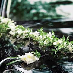 Traine de fleurs sur la voiture des mariés