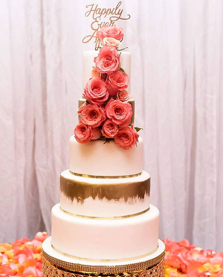 A five tiered wedding cake with peach and gold decorations