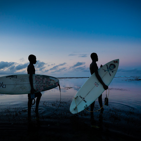Two local surfers walking in the shallows - Vanimo, Papua New Guinea
