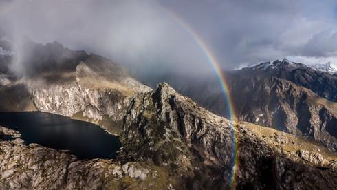 A rainbow forms behind Laguna Cherup - Huaraz, Peru