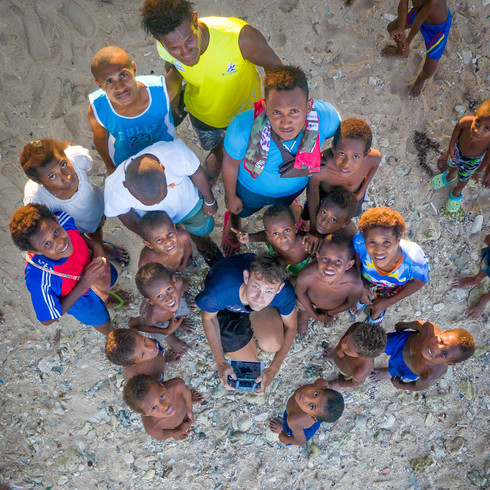 Children from the village of Lido encircle me while I fly my drone - Vanimo, Papua New Guinea