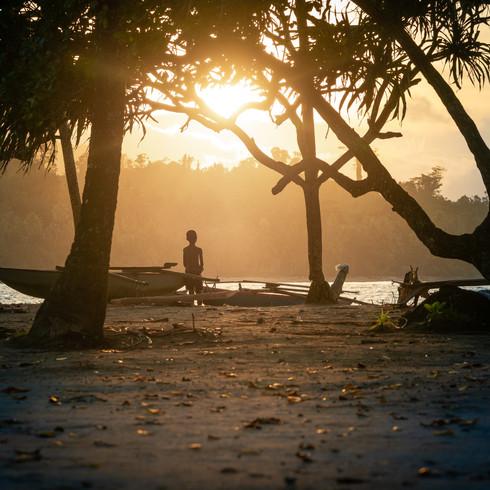 A child enjoys a sunset on the beach - Vanimo, Papua New Guinea