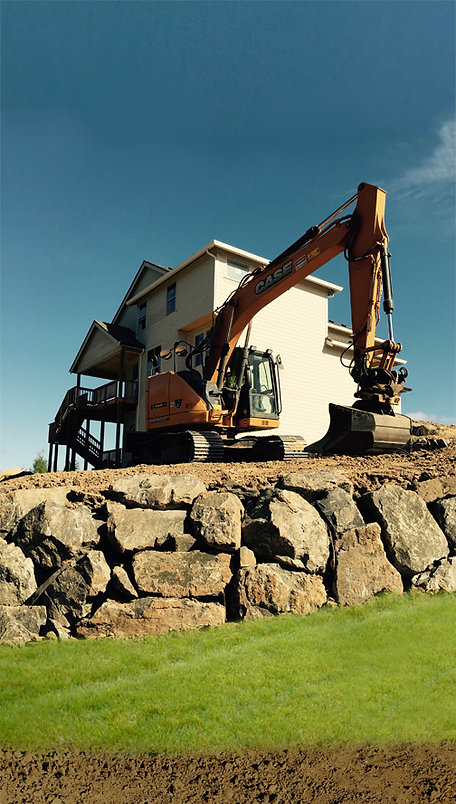 Excavator grading above new residential rock wall