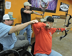 Veteran being coached by a Certified Adaptive Sports Coach at Cinnamon Creek Archery.