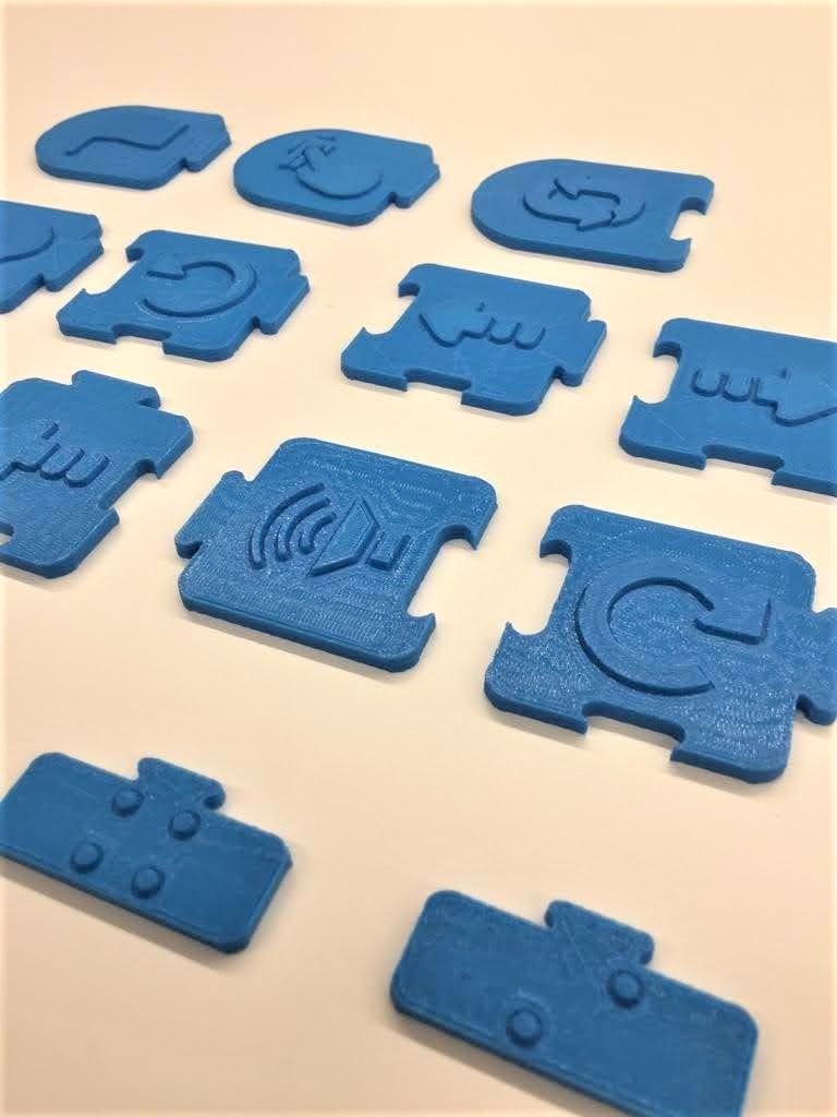 Bloques de programación táctiles hechos en impresora 3D de color azul, el prototipo 1. Contiene 16 piezas distintas con diferentes iconos en relieve..