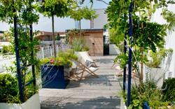 Rooftop champêtre autour d'un salon de jardin entouré de massifs de vivaces fleuries