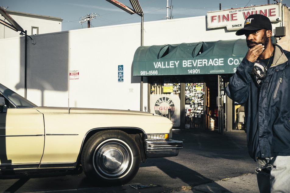 Scenes-Man walking in front of a liquor