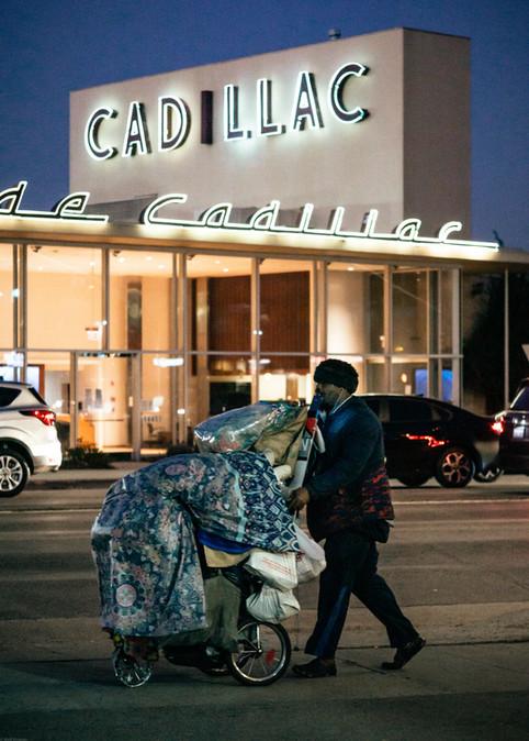 Scenes-Homeless man pushing a cart passi