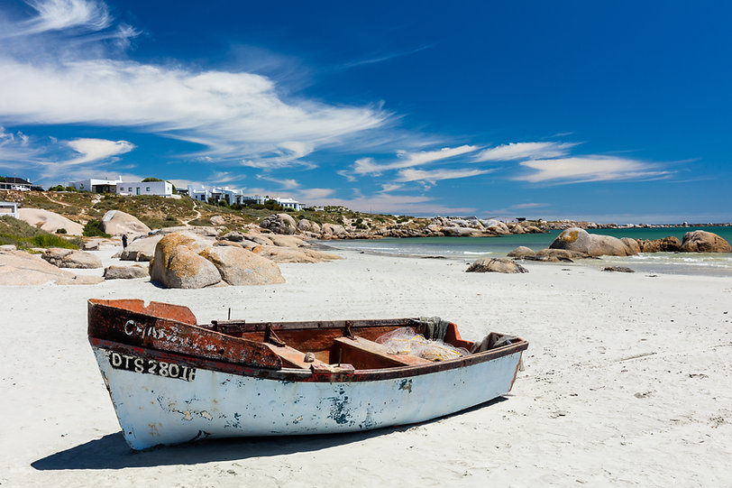 A fishing boat on the white sand of the