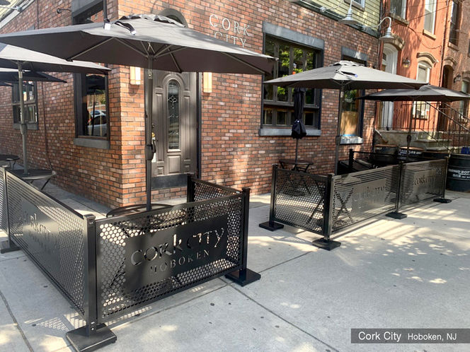 black outdoor bar seating barricade partitions with black umbrellas