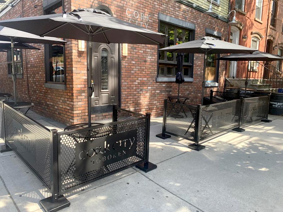 Black sidewalk cafe fencing with custom lasercut logos