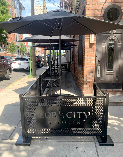 Outdoor seating patio with black partitions, furniture, and umbrellas