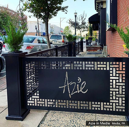 outdoor seating barriers with planters and a custom logo panel