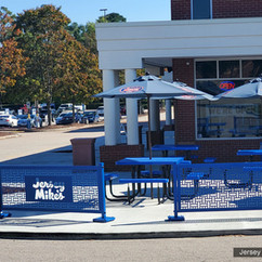 Custom color-matched patio partitions with a lasercut logo panel.