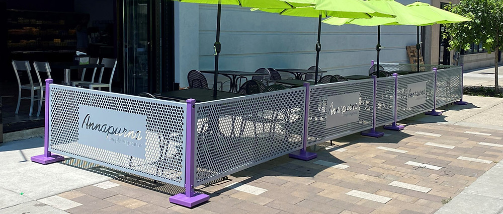 Al fresco dining area with gray and purple barriers and bright green umbrellas