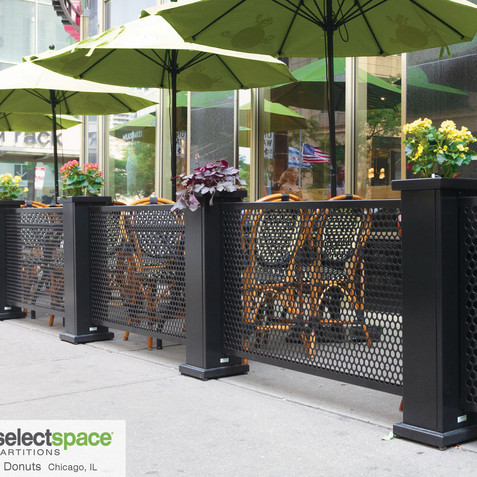 SelectSpace black sidewalk partitions with built-in planter stands.
