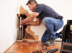 Middle aged man repairing burst water pi