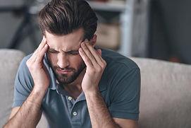 man-with-migraine-headache-massaging-his
