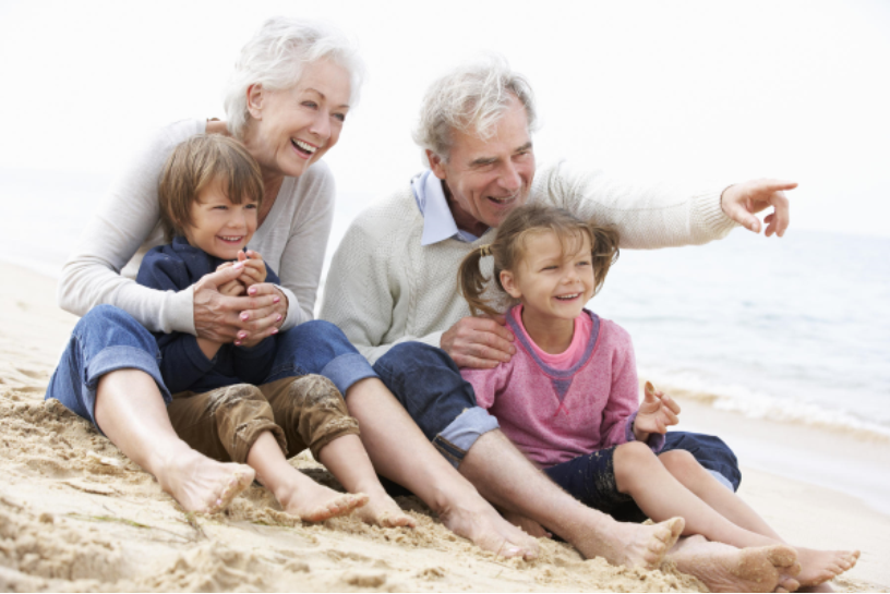photo of happy active senior grandparents with their two grandchildren enjoying a special moment sitting on the beach barefoot in the sand wearing jeans and sweaters while pointing out to the ocean