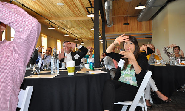 2014 Leadership Institute - A women frames her hands in front of her face while sitting at a table.