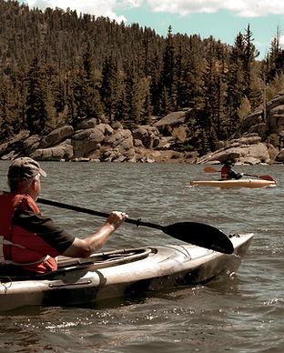 three-men-riding-kayaks-on-body-of-water