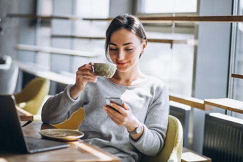 mujer-sentada-cafe-tomando-cafe-trabajan