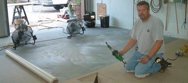 Installation d'une membrane de Decking sur un plancher de garage en béton.