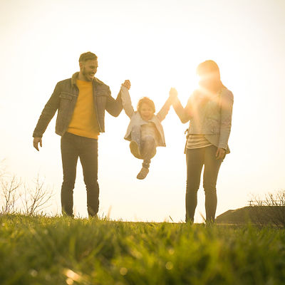 Happy parents playing with their daughter in the park. Space for copy..jpg