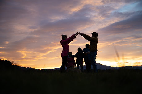 Silhouette of a family outside under a b