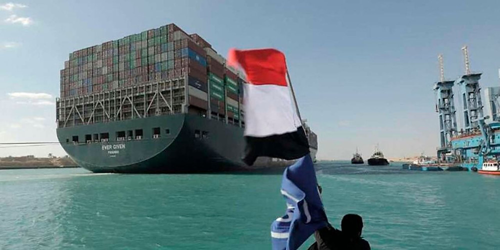 A picture released by Egypt's Suez Canal Authority on March 29, 2021, shows a man waving the Egyptian flag after Panama-flagged MV 'Ever Given' container ship was fully dislodged from the banks of the Suez.