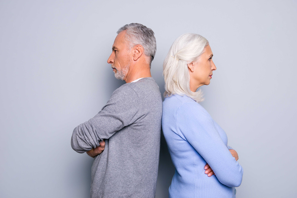 older couple standing back to back