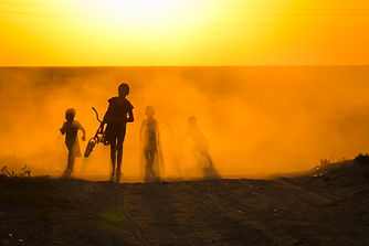 Kids walking through dust of Moynaq at sunset in Uzbekistan