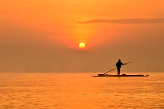 Fisherman paddles on Lake Victoria at sunset in Uganda