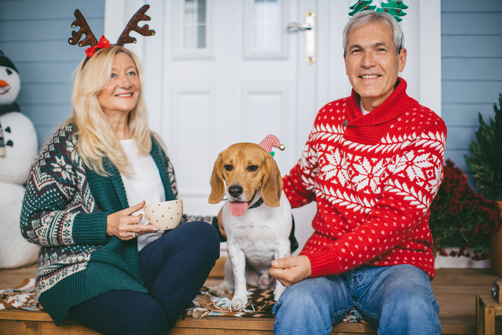 couple with dog wearing christmas outfits, sitting on porch