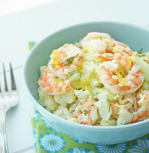 Blue bowl of shrimp cauliflower salad garnished with lemon and dill on top