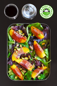 Tin box filled with mixed greens, prosciutto wrapped peaches, salad dressing, and garnished with walnuts and pistachios