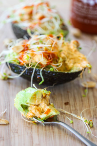 Two Thai styled avocados with garnish of bean sprouts and siracha sauce