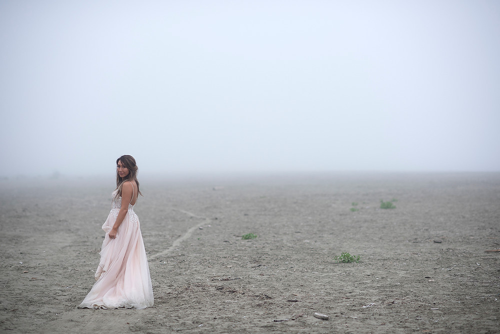 bride stands in the fog at tofino beach wedding at Long Beach Lodge. Photographed by Kaitlyn Shea