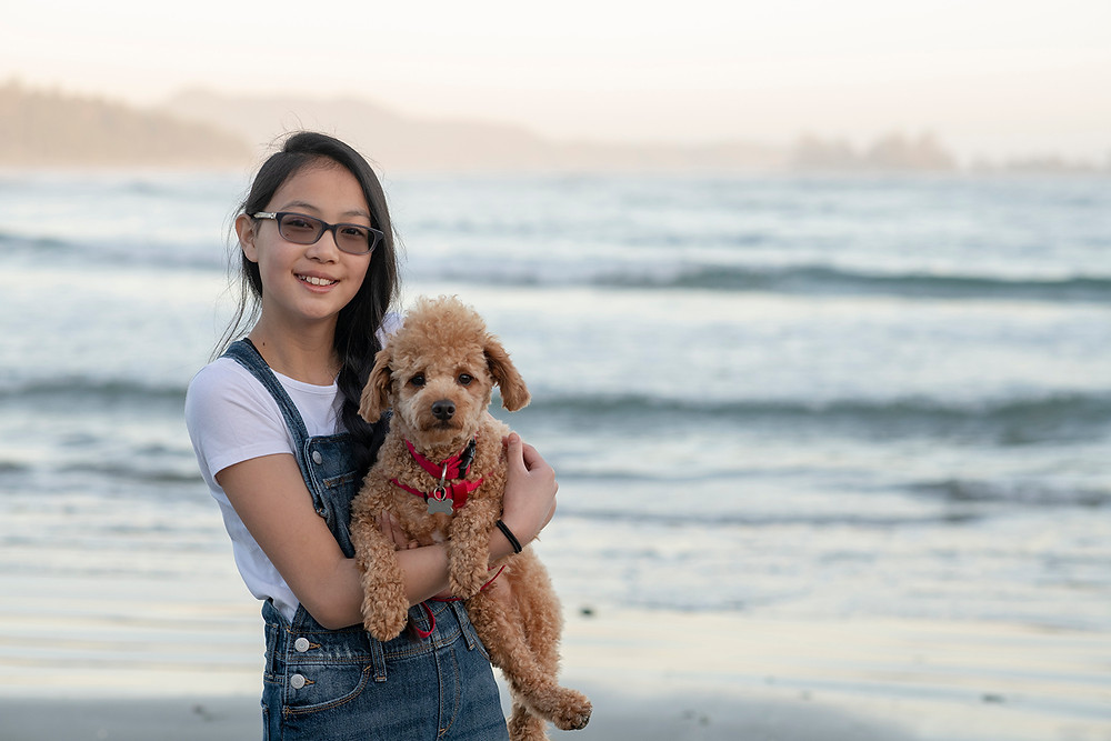 girl holds her dog during family pictures in Tofino | Photographed by Kaitlyn Shea