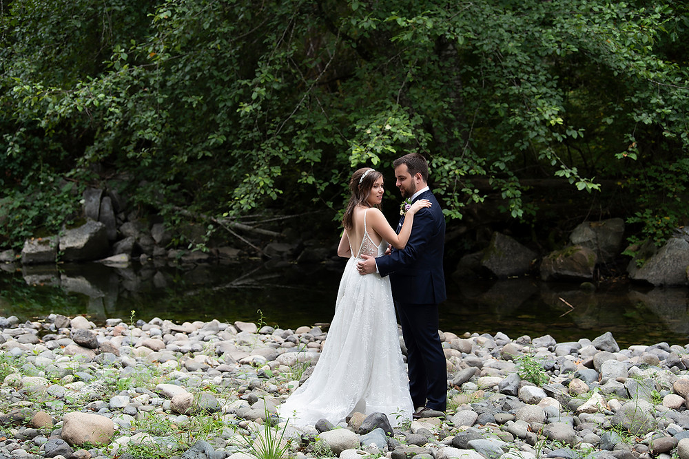 Groom and bride stand by a beautiful creek in Port Alberni at their Vancouver Island wedding. Photographed by Kaitlyn Shea.