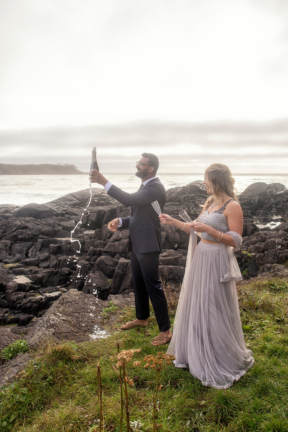 Man pops champagne at their small wedding in Tofino. Photographed by Tofino wedding photographer Kaitlyn Shea.