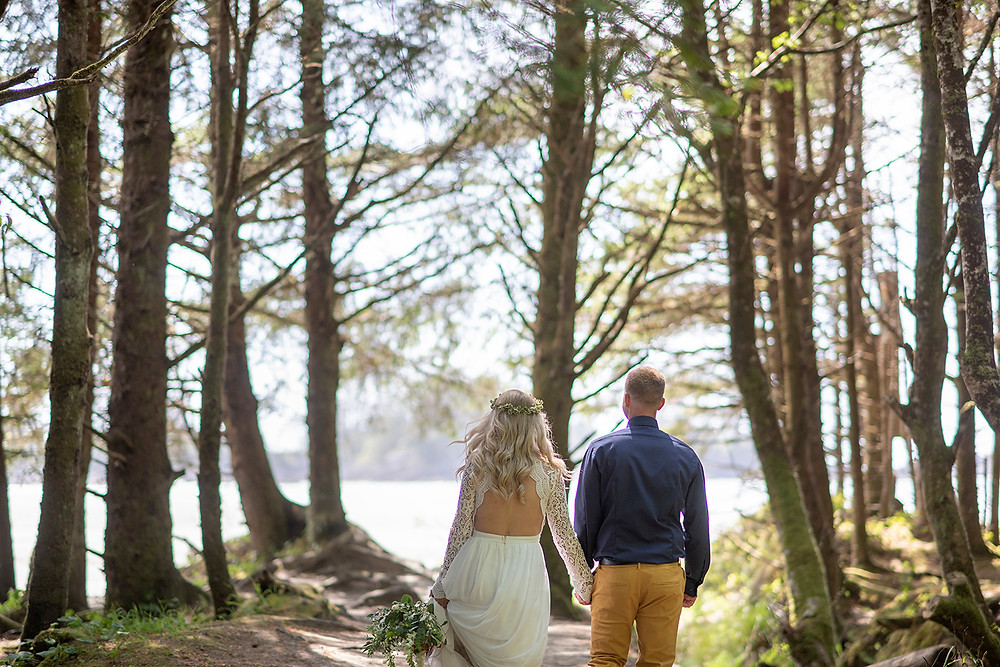 bride and groom walking through forest at Tofino wedding. Photographed by Kaitlyn Shea