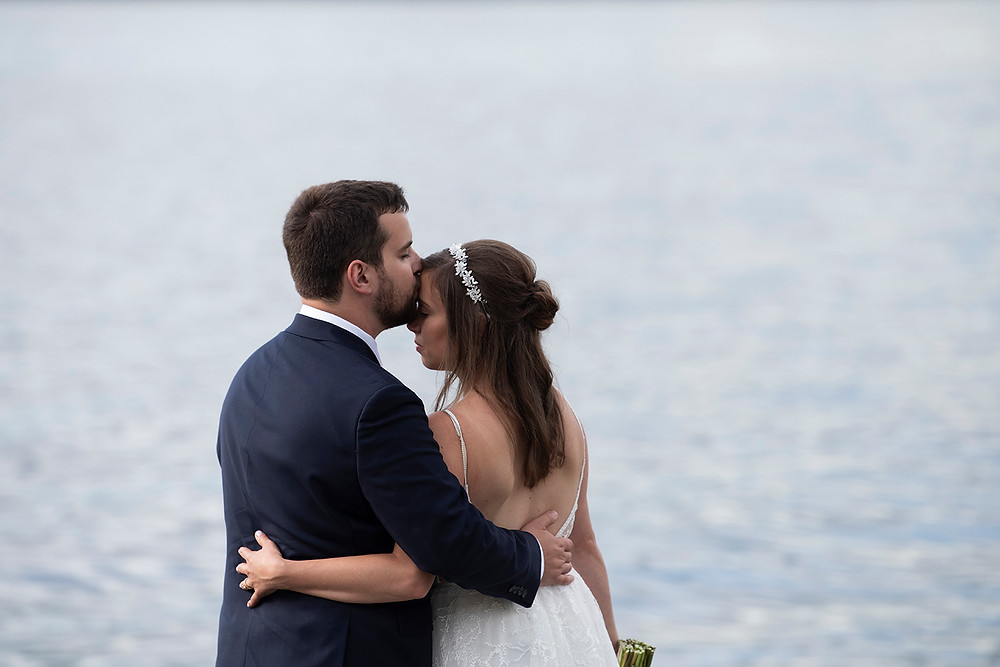 Groom kisses bride on the forehead at their wedding in August on Vancouver Island. Photographed by Kaitlyn Shea.