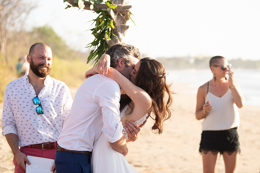 Couple shares their first kiss as a married couple at their destination wedding in Playa Grande, Costa Rica. Photographed by Kaitlyn Shea.