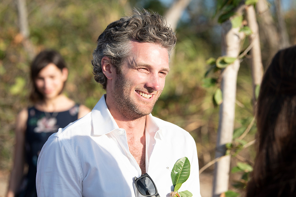 Groom smiles at bride at destination wedding in Playa Grande, Costa Rica. Photographed by Kaitlyn Shea.