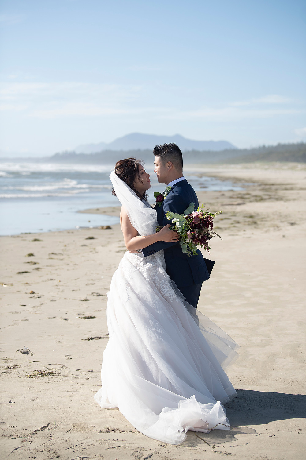 Bride and groom hold each other on the beach at their Ucluelet wedding at Black Rock Resort. Photographed by Ucluelet Photographer Kaitlyn Shea.
