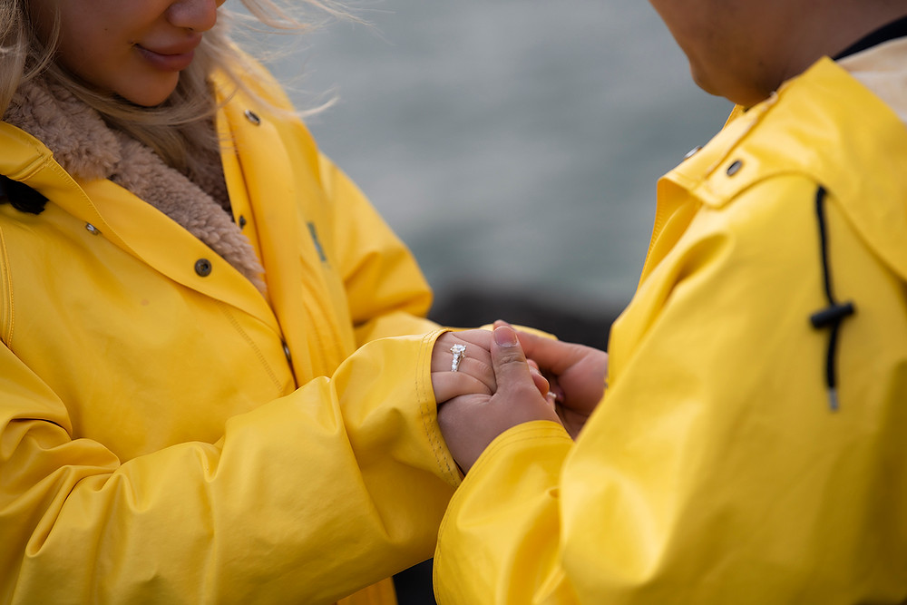Woman looks at her engagement ring after surprise proposal in Tofino. Photographed by Kaitlyn Shea.